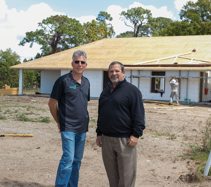 Florida Home Partnership's Construction Manager, Jody Fitzgerald and Executive Director, Mike Morina in front of one of seven Net Zero Energy Homes being constructed in Ruskin, FL